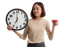Young Asian business woman with tomato juice and clock Stock Photography