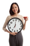 Young Asian business woman with tomato juice and clock Stock Photo
