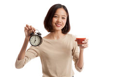Young Asian business woman with tomato juice and clock Royalty Free Stock Photography
