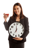 Young Asian business woman with tomato juice and clock. Stock Photography