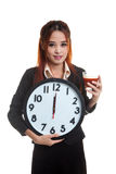 Young Asian business woman with tomato juice and clock. Royalty Free Stock Photo