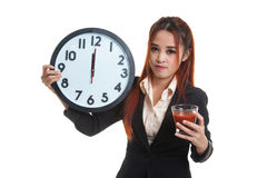 Young Asian business woman with tomato juice and clock. Royalty Free Stock Photography
