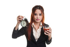 Young Asian business woman with tomato juice and clock. Royalty Free Stock Image