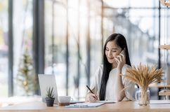 Young asian business woman using laptop and writing on notebook. Woman officer hard working communicate with customer and record Royalty Free Stock Image