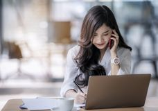 Young asian business woman using laptop and writing on notebook. Woman officer hard working communicate with customer and record Stock Photos