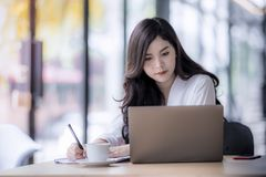 Young asian business woman using laptop and writing on notebook. Woman officer hard working communicate with customer and record Royalty Free Stock Images