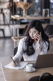 Young asian business woman using smartphone. And write on notebook, woman officer hard working communicate with customer and record Stock Image