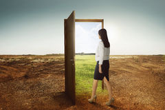 Young asian business woman walking to the open door going to green environment. On cracked land background stock image