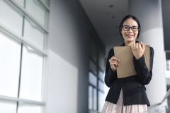 Young Asian business woman wear suit holding file document royalty free stock photos