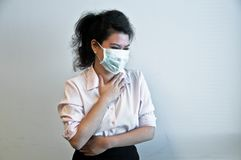 Business woman wear hygiene mask and sick. Young Asian business woman wears a green hygiene mask and feel sick with sore throat Stock Photos