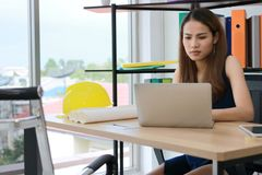 Young Asian business woman working with laptop on the workplace in office stock photo
