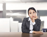 Young asian business woman working at office desk and thinking s Stock Images