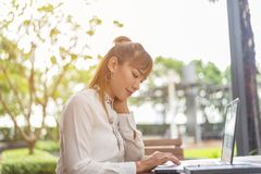 Young asian business woman working in office using laptop computer and digital tablet. royalty free stock image