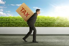 Young asian businessman carrying heavy box of TAX. Taxation concept stock image