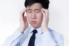 Young Asian businessman facing headache / migraine problems in white isolated Stock Image