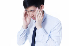 Young Asian businessman facing headache / migraine problems in white isolated Royalty Free Stock Photography