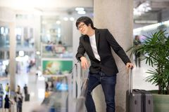 Young asian man waiting in airport terminal Royalty Free Stock Photography
