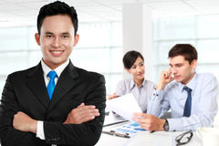 Young asian businessman, with his team behind. isolated in white Royalty Free Stock Images