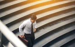 Young asian businessman holding briefcase and running to meeting. At underground office building Stock Photos