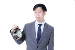 Young Asian businessman holding a clock in unpleasant face expression - business and time concept. Stock Photo