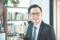 Businessman holding coffee cup and smiling in office. Young asian businessman holding coffee cup and smiling in office Stock Photography