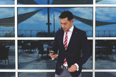 Young asian businessman holding his mobile phone while standing at office building window outdoors Stock Photography