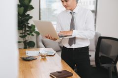 Young asian businessman holding a laptop pc.  royalty free stock photos