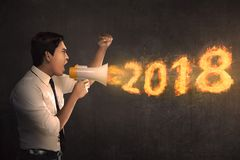 Young asian businessman holding megaphone and shouting 2018 in f. Ire. Happy New Year 2018 Stock Images
