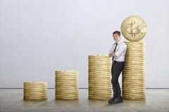 Young asian businessman lean back on bitcoins stack. On grey wall background Stock Images