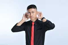 Young asian businessman listening with sign hand close to the ear stock photography
