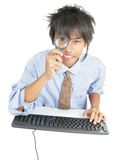 Young Asian businessman peering thru magnifier Stock Photography