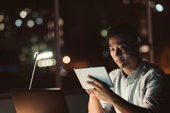 Young Asian businessman working on a tablet late at night Royalty Free Stock Photography