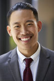 Young Asian businessman smiles to camera, close up, vertical royalty free stock image
