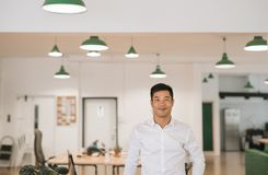 Young Asian businessman smiling confidently while standing in an office Stock Photography