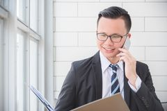 Businessman smiling while using mobile phone at office. Young asian businessman smiling while using mobile phone at office Royalty Free Stock Image
