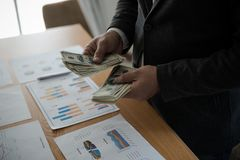 Young asian businessman standing count a dollar bill from his de Stock Image