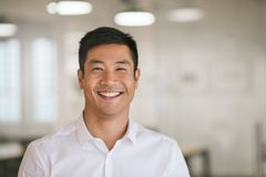 Young Asian businessman standing in an office smiling confidently Stock Photos