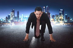 Young asian businessman in start position ready to race. On concrete with city background Stock Photography