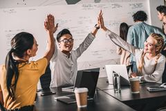 young asian businessman taking high fives to female colleagues at modern stock photos