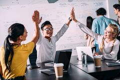 young asian businessman taking high fives to female colleagues at modern stock image