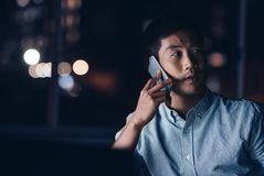Young Asian businessman talking on his cellphone while working l Stock Photography