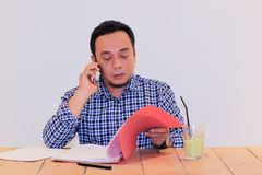 Young Asian businessman talking on the phone-checking some document file data. Young Asian businessman talking on the phone-checking document file report data stock photography