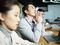 Young asian businessman thinking during meeting Royalty Free Stock Photo
