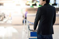 Young asian businessman with trolley in airport terminal. Young asian businessman with his luggage on airport trolley waiting for check in at airline counter in Stock Photos