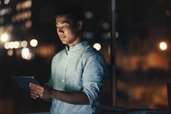 Asian businessman using a tablet late at night Stock Photo