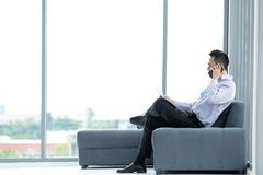 Young Asian businessman using mobile smartphone sitting on sofa royalty free stock images