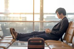 Young Asian businessman using smartphone in airport terminal stock photo