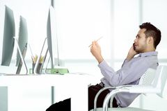 Young Asian businessman using smartphonesitting at desk royalty free stock photography