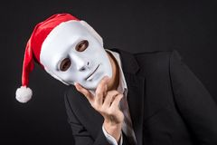 Young Asian businessman wearing white mask and santa hat. Male anonymous worker wearing party costumes on black background. Christmas and New Year holiday Royalty Free Stock Photography