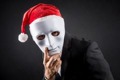 Young Asian businessman wearing white mask and santa hat. Male anonymous worker wearing party costumes on black background. Christmas and New Year holiday Stock Photo